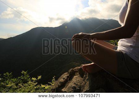 young yoga woman on sunrise mountian peak