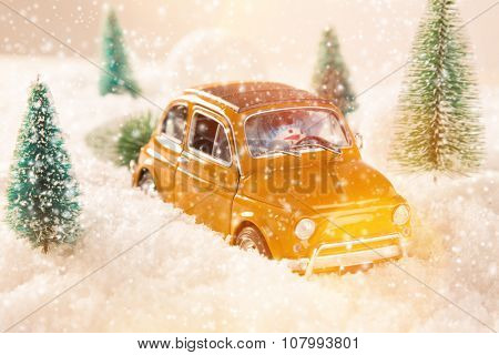 Miniature yellow car with spruce trees. Christmas theme.