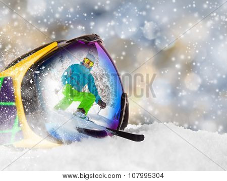 Colorful ski glasses with skier on snow. Winter ski theme.