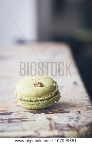 Close Up Of Pistachio Macaroon On Rustic Table