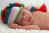 pic of newborn baby girl  - A sleeping baby girl wearing a striped hat - JPG