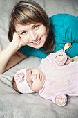 foto of babygro  - Young smiling mother with her baby daughter in pink crawlers lying on bed - JPG