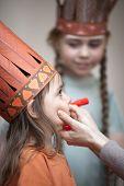 Постер, плакат: Little Girls Preparing To Play Indians