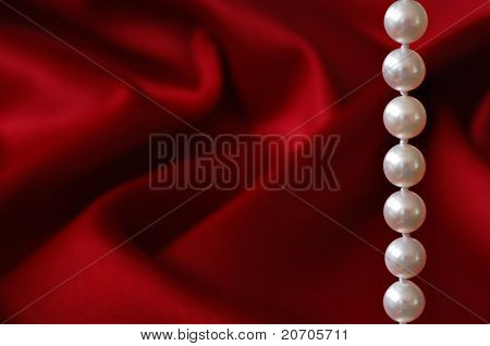 Elegant background image of beautiful cultured pearls against a red satin background.  Macro with shallow dof and copy space.  Selective focus limited to the pearls.