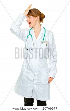 Surprised medical doctor woman striking her forehead isolated on white
