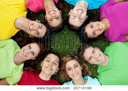 Happy smiling group of young friends staying together outdoor in the park