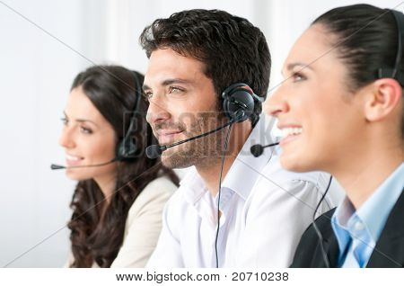 Smiling positive young man with headset and colleagues in a modern call center office