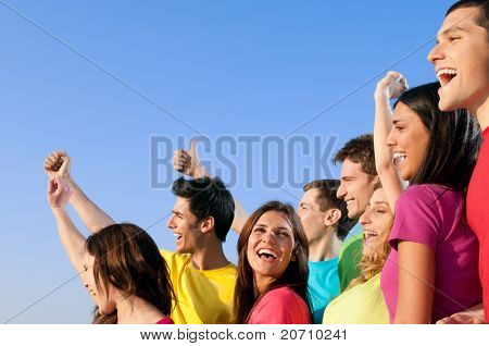 Happy joyful group of young friends staying together with fun outdoor