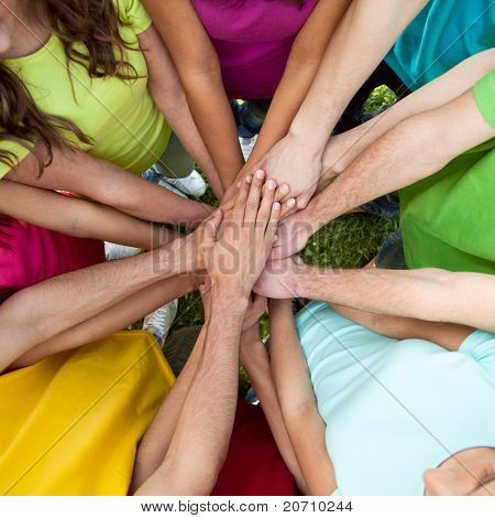 High view of team of friends showing unity with their hands together