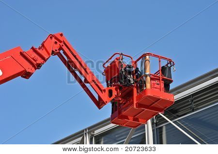 red hydraulic construction cradle against the blue sky