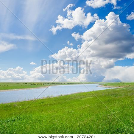green grass with river under cloudy sky