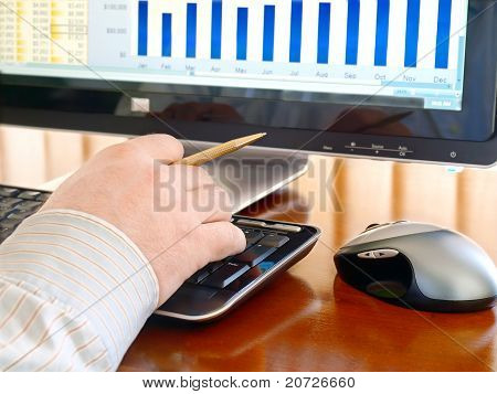 Man's hand with pen typing at a computer keyboard.