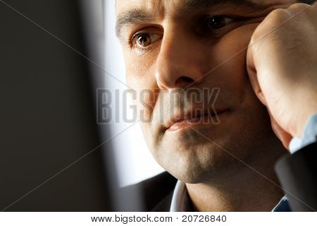 Portrait of thinking man behind laptop, looking at screen