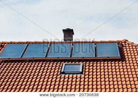 Roof With Solar Panels On A Background Of Blue Sky
