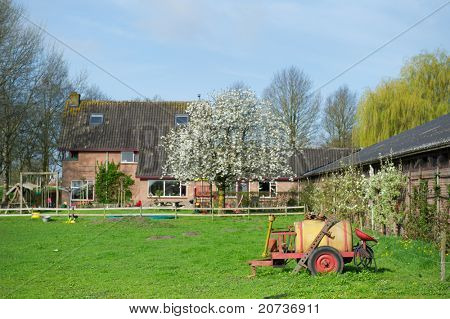 Dutch farm house with work tools and blossom tree