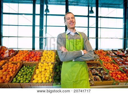 A grocery store owner standing in front of vegetables and fruit