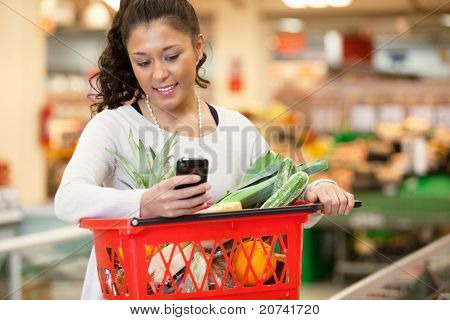 Smiling young woman using mobile phone while shopping in shopping store