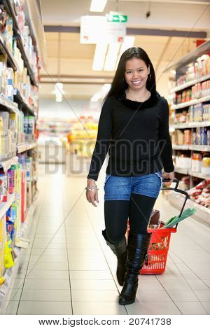 Full length of smiling woman in shopping centre pulling basket while walking and looking at camera