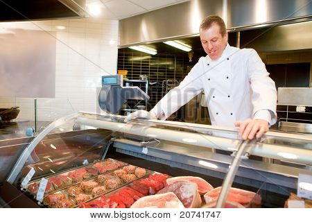A butcher at a fresh meat counter in a grocery store