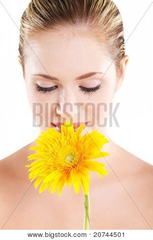 beautiful young woman smelling flower on white
