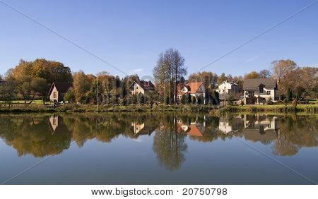 Small Village And Its Reflection In Water