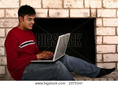 Indian Man Using Laptop In Front Of Fireplace