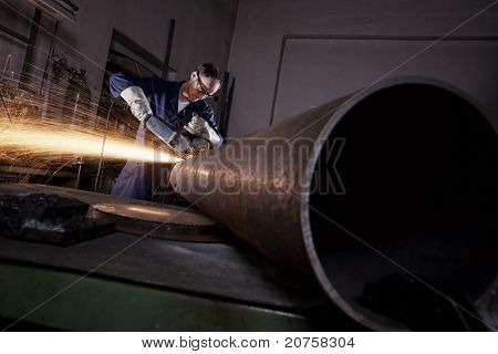 Heavy industry worker cutting steel pipe with angle grinder in workshop.