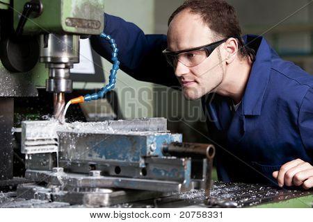 Trabalhador colarinho azul com óculos de segurança em fresadora na oficina.
