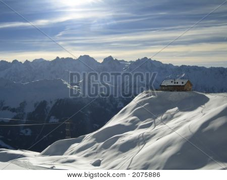Chalet On Mountaintop In Swiss Alps In Winter
