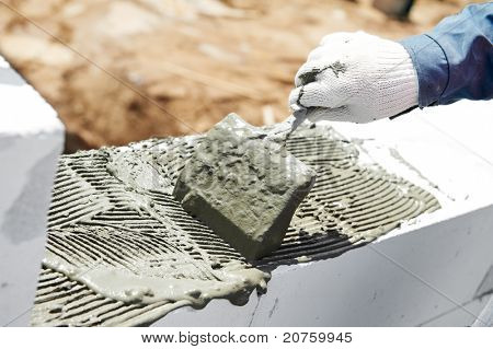 bricklaying construction process of cement mortar adding with trowel putty knife