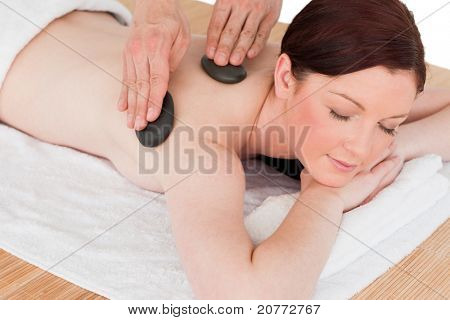 Portrait of an attractive red-haired female posing while receiving a massage in a spa center