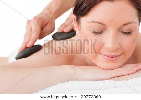 Portrait of a serene red-haired female posing while receiving a massage in a spa center