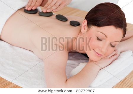Portrait of a beautiful red-haired female posing while receiving a massage in a spa centre