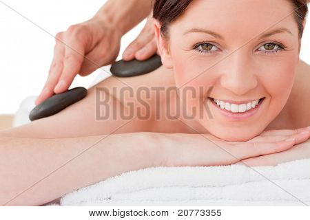 Portrait of a smiling red-haired female posing while receiving a massage in a spa center