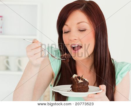 Gorgeous red-haired woman eating some cake in the kitchen in her apartment