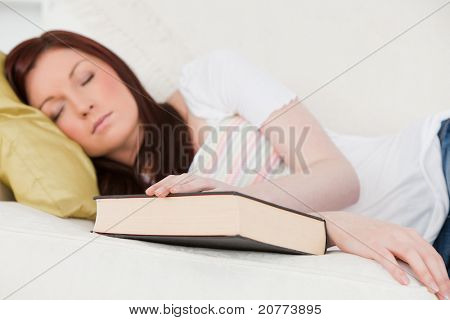 Good looking red-haired girl having a rest while studying on a sofa in the living room