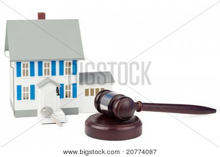 Grey toy house model with a key and a brown gavel against a white background