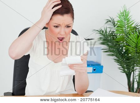 Young attractive red-haired female being surprised by the amount of the receipt while sitting at a desk