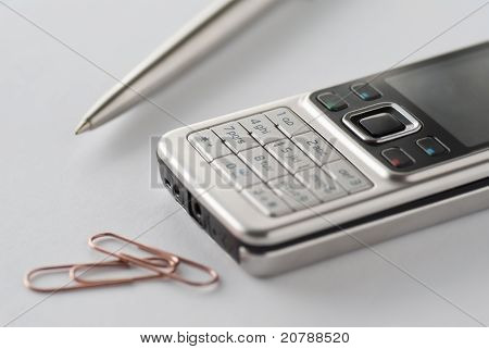 Cell phone with pen and paperclips