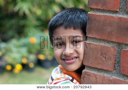 An handsome Indian kid looking shy at a local park