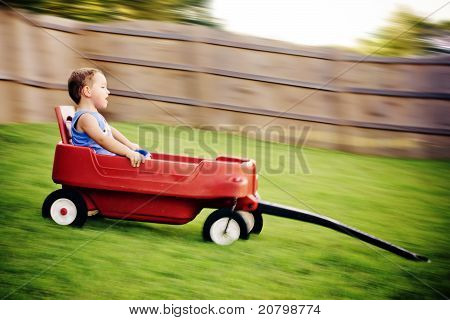 Young boy zooms downhill in wagon in image with motion blur.