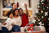 Cheerful African family making selfie together for Christmas poster