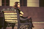 Young woman with long curly hairs sitting on bench in city street. Stylish fashion model in long ves poster