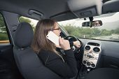 Young female driver using cellphone while driving a car poster