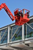 image of cherry-picker  - red hydraulic construction cradle against the blue sky - JPG