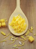 picture of shredded cheese  - grated cheese on a wooden spoon - JPG