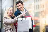Couple, man and woman, at shop window doing Christmas shopping poster