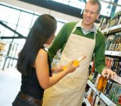 stock photo of grocery store  - Woman standing with smiling store worker while holding drink bottle in grocery store - JPG