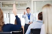 Businessman in seminar pointing towards woman raising hand to say a question. Human resource manager poster