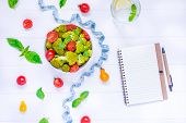 Top View Salad Bowl With Cherry Tomatoes, Broccoli, Measuring Tape And Diet Book On The White Wooden poster